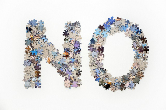 The word NO written in capital letters from a pile of blue and orange jigsaw puzzle pieces with a gray cardboard back. Pictured separated on a white background. Can also be turned upside down to spell ON.